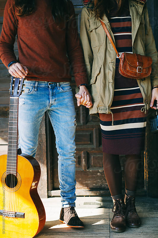 Closeup of hipster couple with a guitar holding hands on a cabin porch. by BONNINSTUDIO for Stocksy United