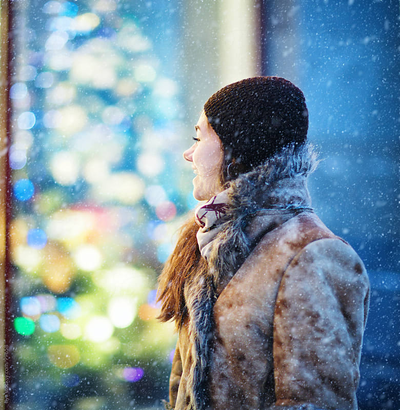 Woman walking in Christmas city at night. by Ilya for Stocksy United