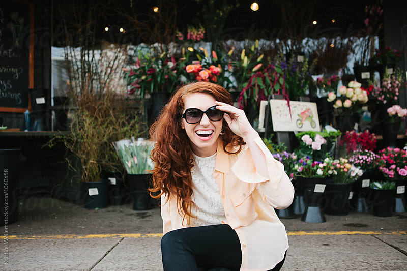 Beautiful woman with red hair laughing outside a flower shop by Kristine Weilert for Stocksy United