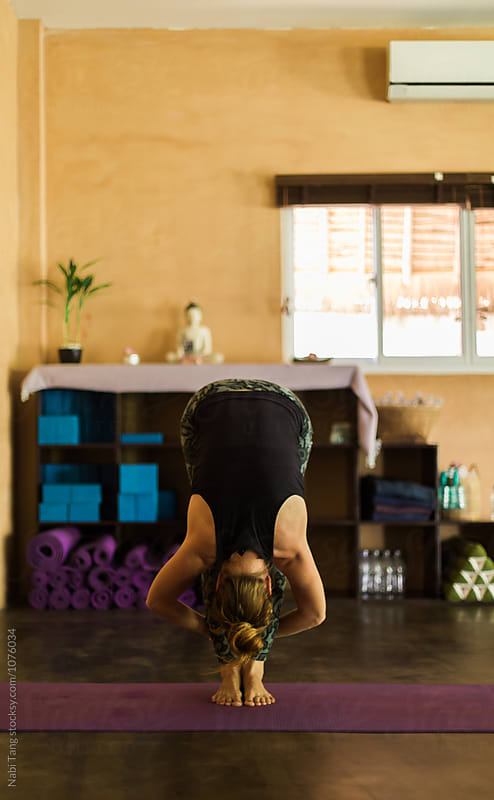 Woman doing Uttanasana (standing forward bend) by Nabi Tang for Stocksy United