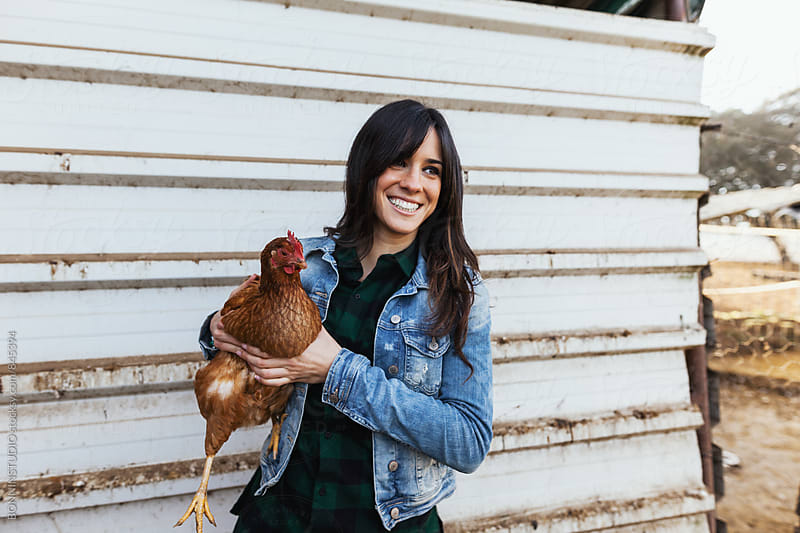 Smiling woman holding a chicken on a farm. by BONNINSTUDIO for Stocksy United
