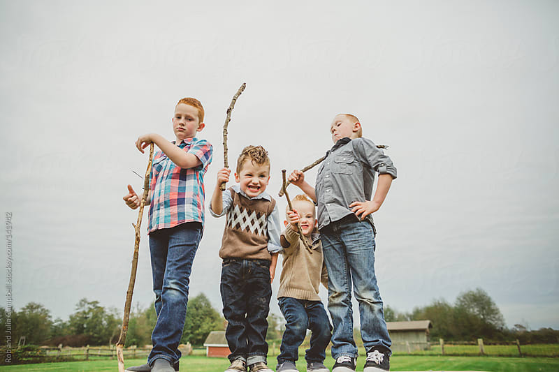 four brothers goofing around with sticks by Rob and Julia Campbell for Stocksy United