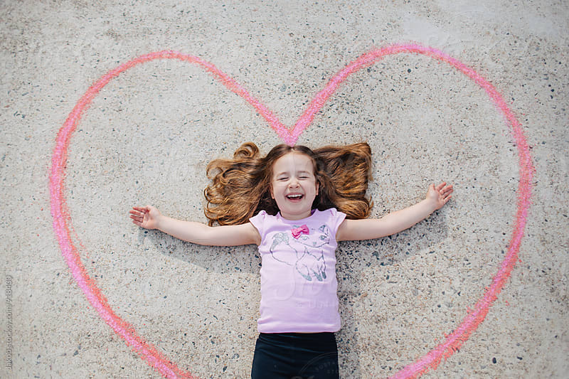 Cute young girl laughing while laying inside of a heart  by Jakob for Stocksy United