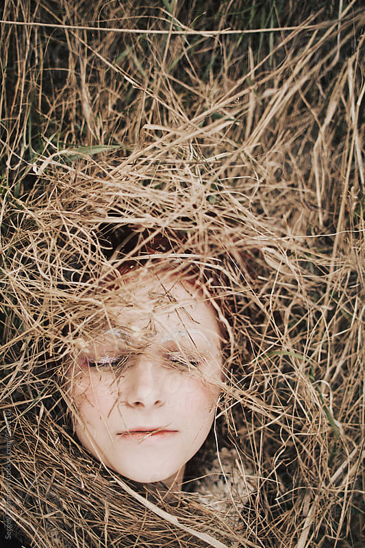 Portrait of a young girl with red hair lying in dry grass by Sergey Filimonov for Stocksy United
