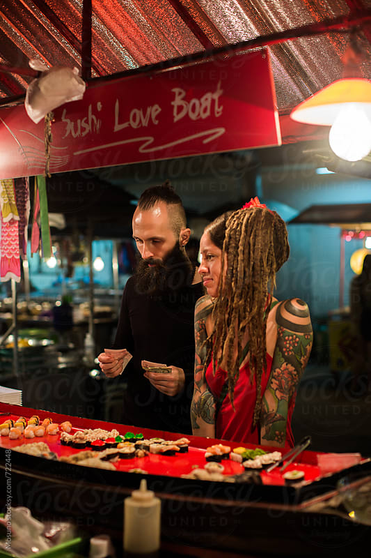 Couple Buying Sushi at the Night Market by Mosuno for Stocksy United