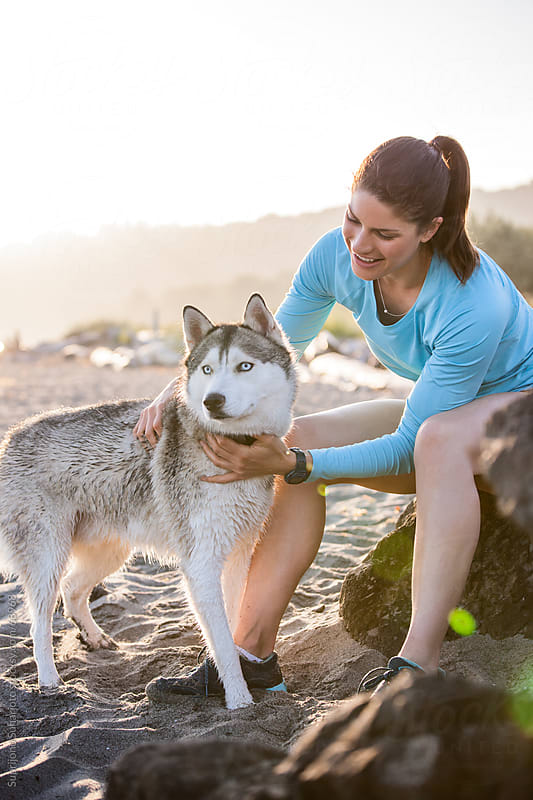 Woman with her dog on the beach by Suprijono Suharjoto for Stocksy United