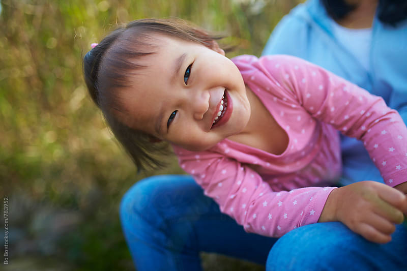 happy little asian girl looking at camera smile in her mother's lap by Bo Bo for Stocksy United