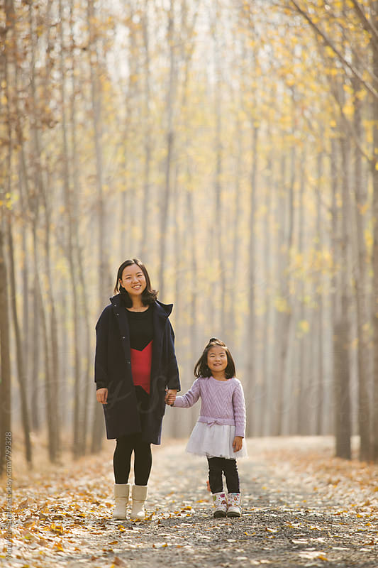 Young mother and daughter standing in autumn wood by Maa Hoo for Stocksy United