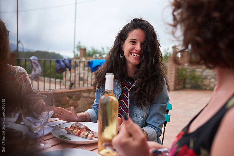 Brunette smiling at friend at dinner table with homemade food outdoor by Guille Faingold for Stocksy United