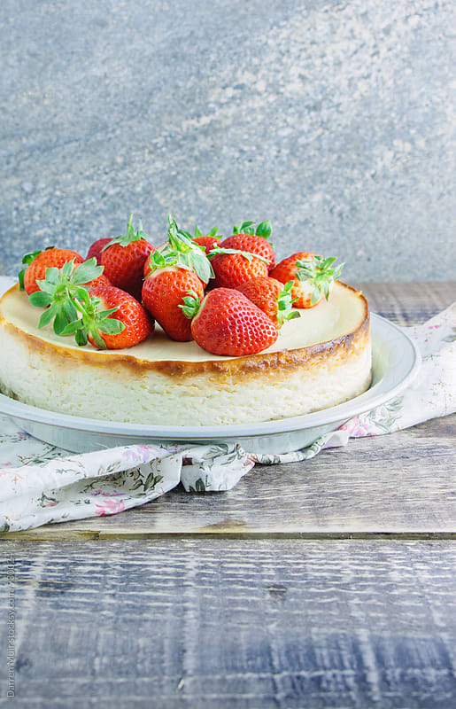 Vanilla cheesecake topped with fresh strawberries. by Darren Muir for Stocksy United