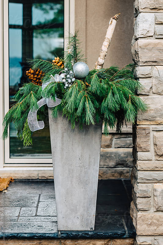 Christmas themed planter on a front porch by Jen Grantham for Stocksy United