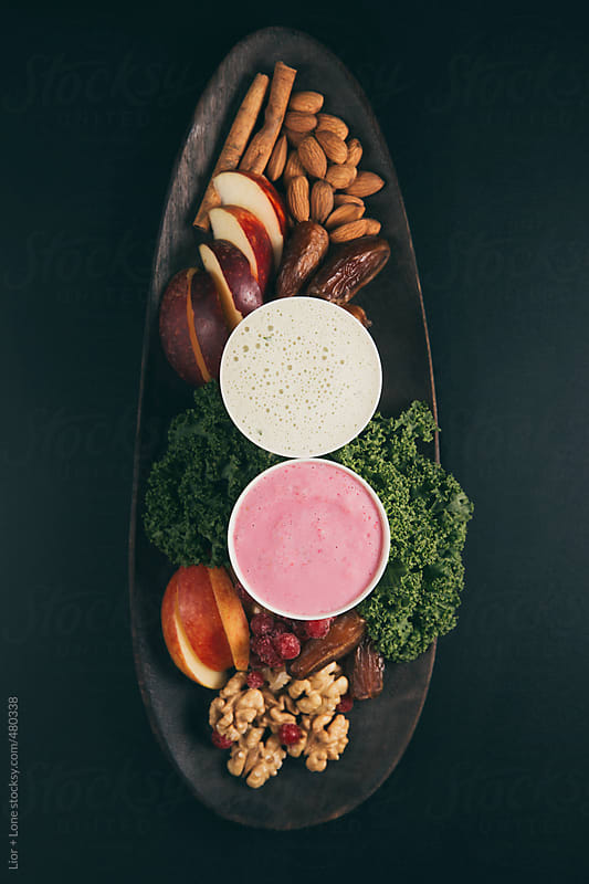 Kale and red berry smoothie on wooden tray with ingredients by Lior + Lone for Stocksy United