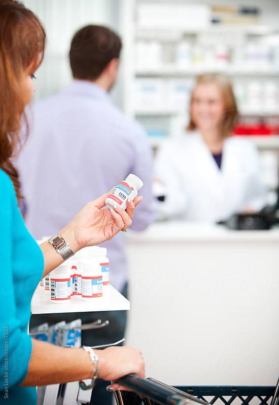 Pharmacy: Woman Reads Instructions on Pill Bottle by Sean Locke for Stocksy United