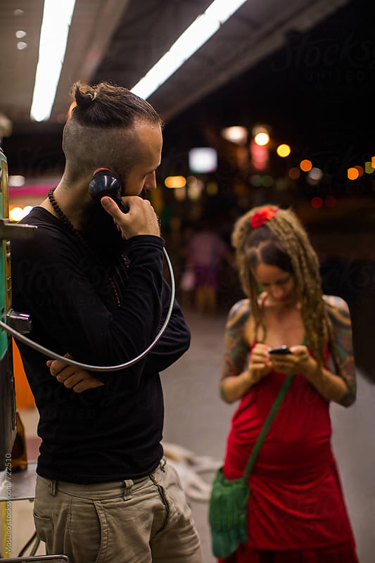 Man Using Public Phone and Woman Checking Her Smartphone by Mosuno for Stocksy United