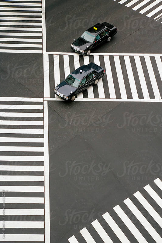 Asia, Japan, Honshu, Tokyo, Ginza, taxi cabs driving across Sukiyabashi Pedestrian Crossing - elevated view by Gavin Hellier for Stocksy United