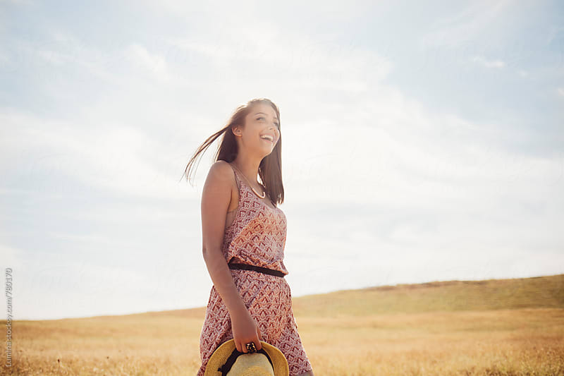 Happy Young Woman Standing in a Field by Lumina for Stocksy United