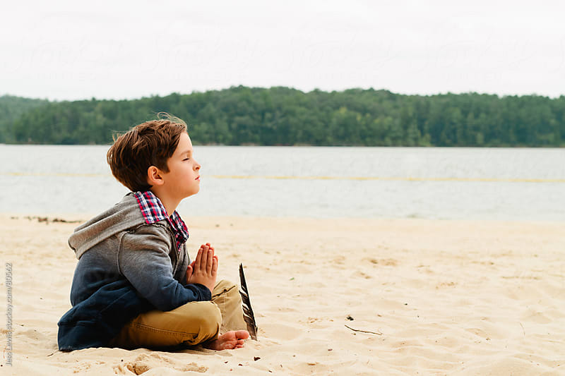 young boy meditating, praying on the beach by Jess Lewis for Stocksy United