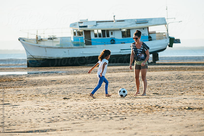 Mother and Daughter play soccer on beach. by Shannon Aston for Stocksy United