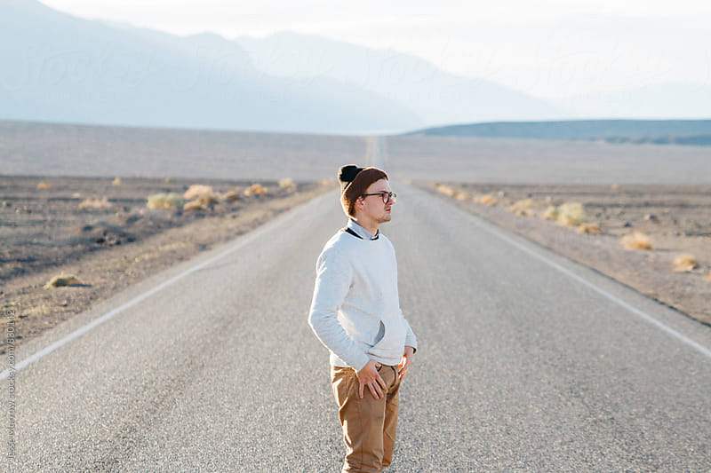 young male in white sweater standing in desert road on adventure by Jesse Morrow for Stocksy United