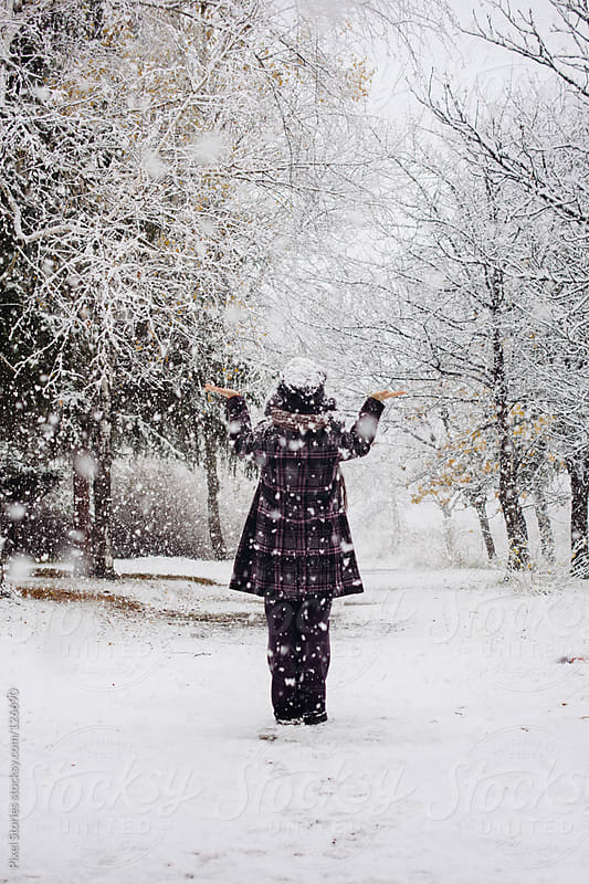 Woman on snowy path by Pixel Stories for Stocksy United