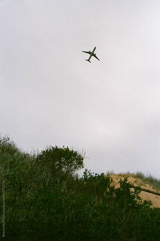 A plane takes off over Wanda Sand Dunes by Reece McMillan for Stocksy United