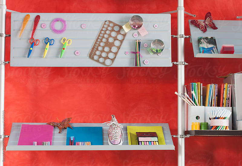 Red wall and shelves of an office or room with lots of office supplies  by Beatrix Boros for Stocksy United