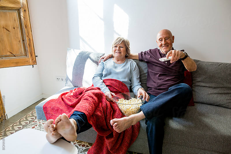 Elderly couple watching a funny movie eating popcorn at home. by BONNINSTUDIO for Stocksy United