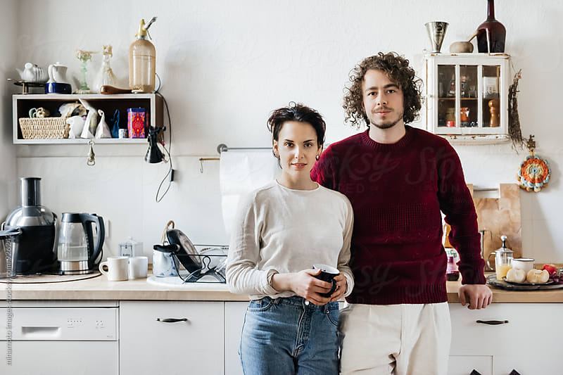 Portrait of a young couple in their kitchen by minamoto images for Stocksy United