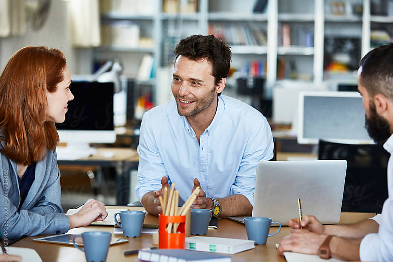 Businessman Leading Colleagues In Discussion At Desk by ALTO IMAGES for Stocksy United