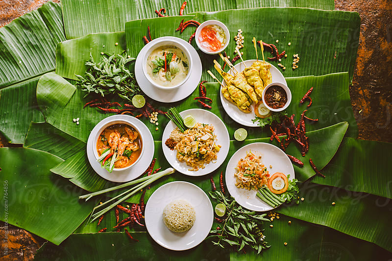 Variety of authentic thai traditional meal set on green banana leaves by Nabi Tang for Stocksy United