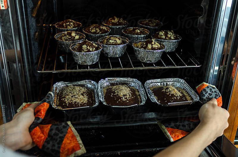 Delicious muffin cakes on cooling rack being holded by beautiful cook by Gabriel Diaz for Stocksy United