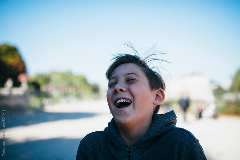 Young handsome boy laughing outside by Trent Lanz for Stocksy United