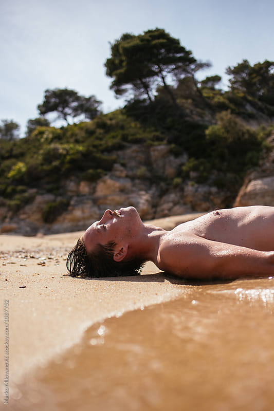Young man sunbathing at seaside by Marko Milovanović for Stocksy United