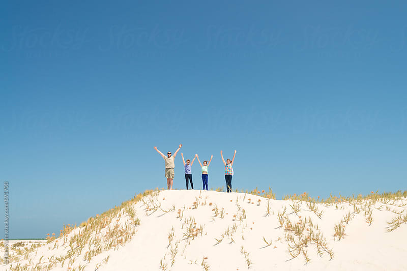 a father with his 3 daughters jumping in sand dunes by Gillian Vann for Stocksy United