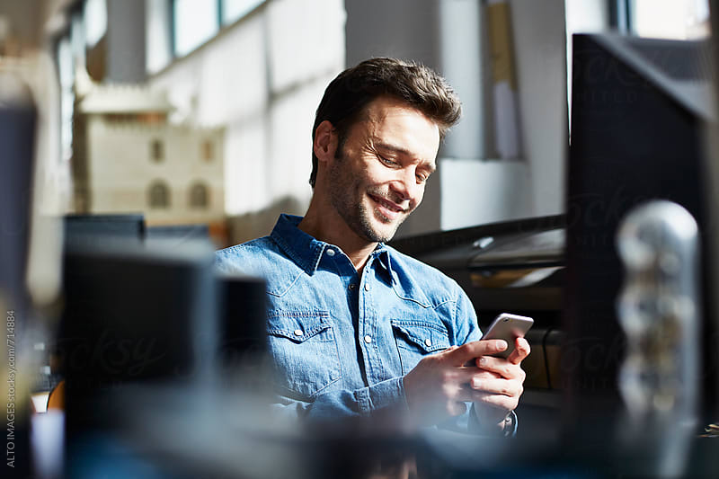 Businessman Using Mobile Phone In Office by ALTO IMAGES for Stocksy United