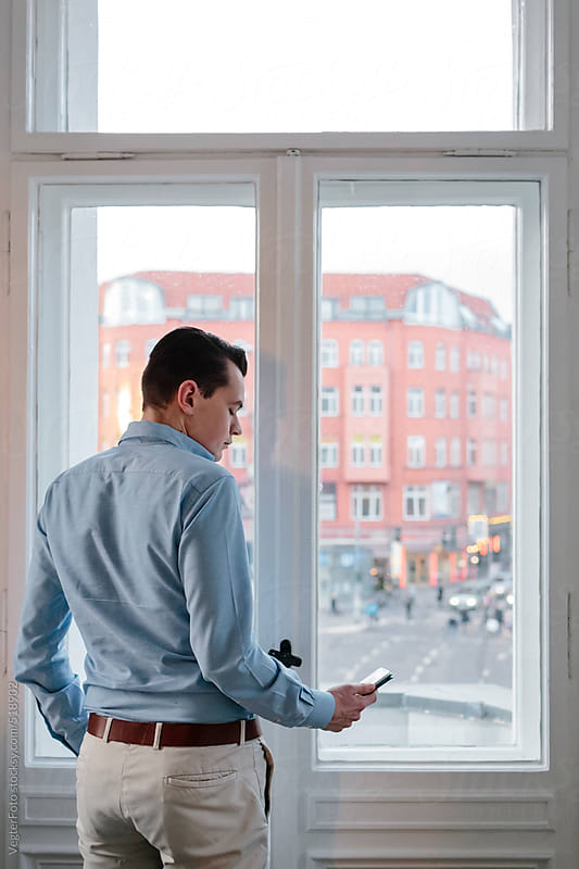 Businessman With Smartphone In front Of Office Window by VegterFoto for Stocksy United