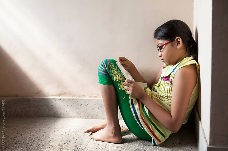 Teenage girl is reading a book by PARTHA PAL for Stocksy United