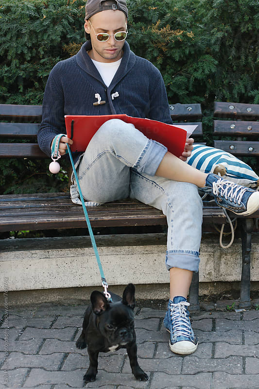 Young male student reading his script on the bench and spends time with his dog  by Evil Pixels Photography for Stocksy United
