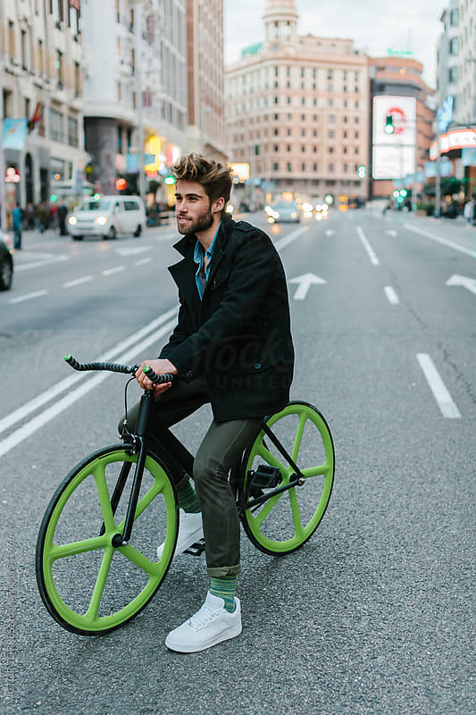Young Man Riding a Custom Fixie on a Crowded Street  by VICTOR TORRES for Stocksy United