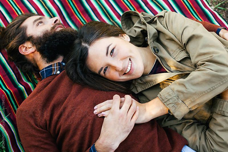Portrait of a smiling woman resting with her boyfriend on a striped blanket. by BONNINSTUDIO for Stocksy United