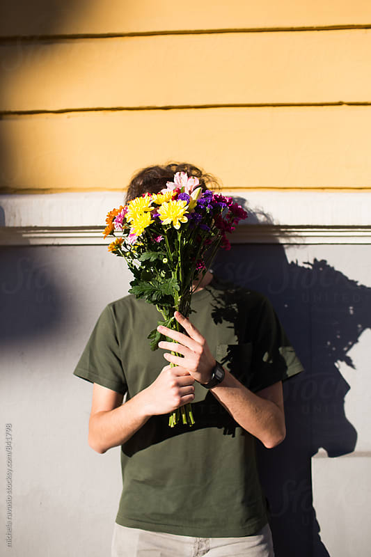 Man with face covered with a bouquet of flowers by michela ravasio for Stocksy United