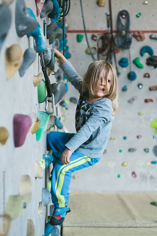 casual young boy with long hair hanging with one hand on an indoor climbing wall by Leander Nardin for Stocksy United