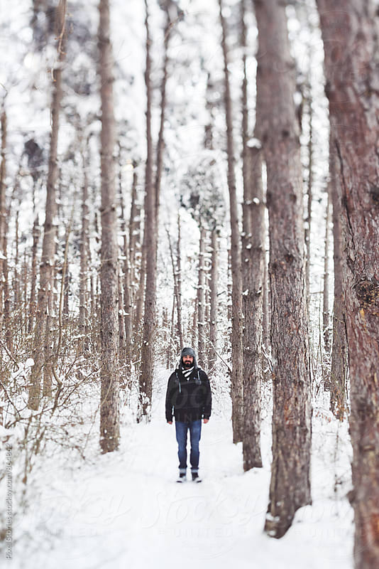 Young man standing on snowy forest path by Pixel Stories for Stocksy United