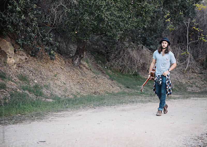 Young musician walking down a dirt trail with guitar in hand by Emmanuel Hidalgo for Stocksy United
