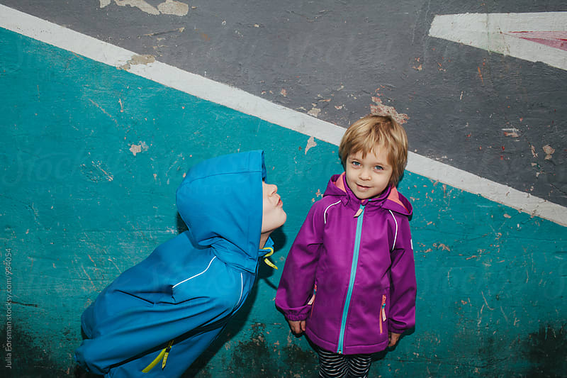 Bright, urban image of a little girl amused by her brother's antics. by Julia Forsman for Stocksy United