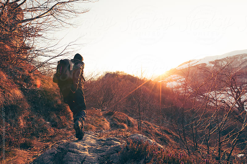 Hiker along a mountain path at sunset by michela ravasio for Stocksy United
