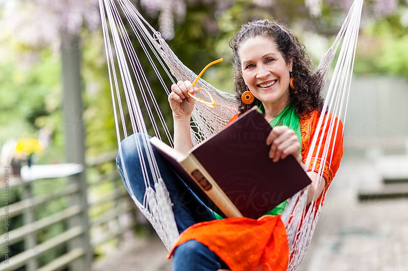 Middle age woman reading a book sitting on a hammock by Suprijono Suharjoto for Stocksy United