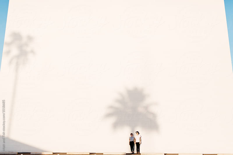 Couple standing in shadow of a Palm Tree by Matt and Tish for Stocksy United