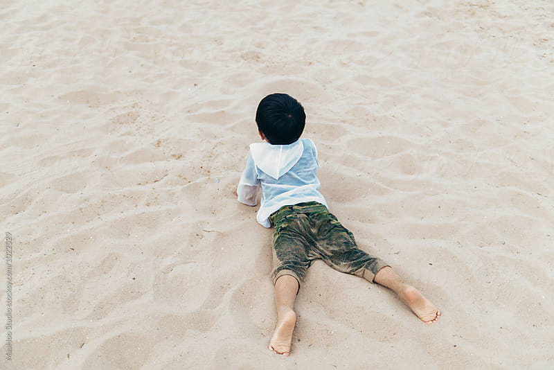 Little boy lying on beach by Maa Hoo for Stocksy United
