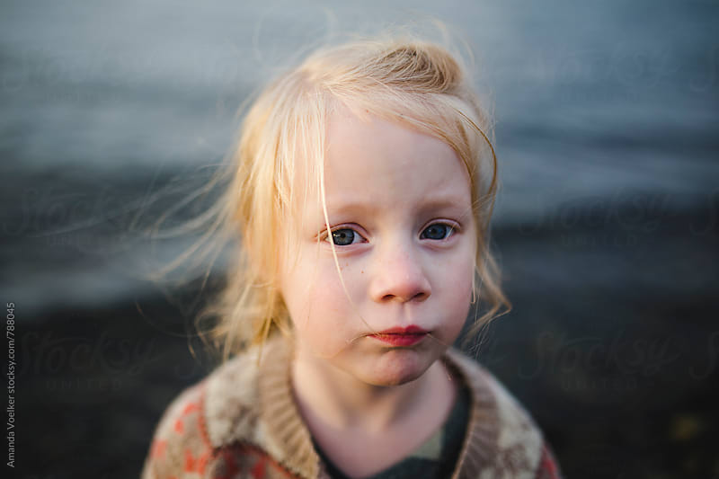 Portrait of a little girl against the dark water by Amanda Voelker for Stocksy United